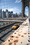 Brooklyn Bridge, New York City. Yellow cab crosses Brooklyn Bridge in New York with financial district in the background. Selective focus on the foreground metal Stock Photography