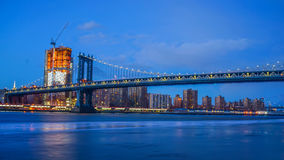Brooklyn Bridge and New York City Skyline nigh. Brooklyn Bridge and NYC Skylinet night with reflection of  the skyline on East River Royalty Free Stock Images