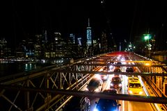 Brooklyn bridge in New York at night with cars passing royalty free stock photos