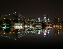 Brooklyn Bridge by night reflect in east river and new york skyline. freedom tower Royalty Free Stock Photos