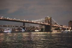Brooklyn Bridge at Night Water Reflections. Brooklyn Bridge in New York City, Water Reflections and light strung across the iconic, historical structure royalty free stock image