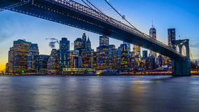 Brooklyn Bridge and NYC Skyline during Sunset. Brooklyn Bridge crosses East River with NYC skyline reflection Stock Photo