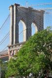 Brooklyn Bridge pillar and green trees in New York Stock Images