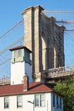 Brooklyn Bridge pillar with house with white tower. NEW YORK - SEPTEMBER 13: Brooklyn Bridge pillar with house with white tower a sunny summer day on September Royalty Free Stock Photography