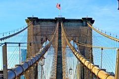 Brooklyn Bridge Simetry. American flag on the top of the brooklyn bridge royalty free stock image