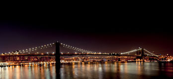 Brooklyn Bridge from South Street Seaport. (Pier 17). Both Brooklyn Bridge and Manhattan Bridge are visible at night in this picture. The Brooklyn Bridge is one Stock Photography