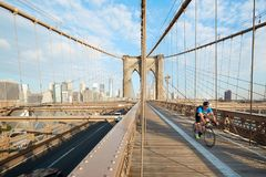 Brooklyn Bridge in a sunny morning with man cycling, New York Stock Photo