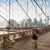 Brooklyn bridge at sunset, New York City. Blured runner running across Brooklyn bridge. New York City Manhattan downtown skyline in sunset with skyscrapers stock photos