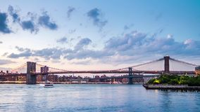 Brooklyn Bridge timelapse. Timelapse with Brooklyn Bridge in transition between day and night, in New York City. Clouds invade the sky, while boats crisscross stock footage