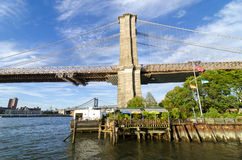 Brooklyn Bridge and Tower with the East River. The Brooklyn Bridge as seen from the Borough of Brooklyn. This view is facing north with the East River to the Royalty Free Stock Image