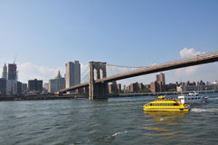 Brooklyn Bridge Water Taxi. A New York Water Taxi heading past the Brooklyn Bridge en route to Manhattan Royalty Free Stock Photo