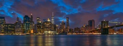 Brooklyn bro och den en internationell handelmitten på skymning Fotografering för Bildbyråer