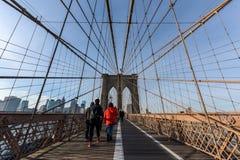 Brooklyn bro på solnedgången med folk som går över arkivfoto