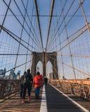 Brooklyn bro på solnedgången med folk som går över arkivfoton