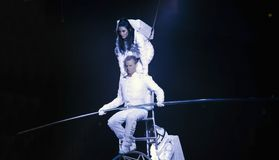 Astronaut dressed performers balance Simet Wheel during Ringling. BROOKLYN, NEW YORK - FEBRUARY 25: Laszlo Simet with partner and wife below dressed as Stock Photo