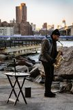 Man plays saxophone for donations in Dumbo Park royalty free stock photo