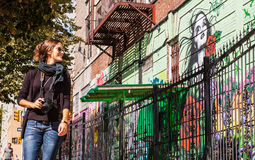 BROOKLYN, NYC, US, September 29 2013: Street art in Williamsburg. Brooklyn. Female photographer with sunglasses walking next to a wall of graffiti in Brooklyn Stock Photography