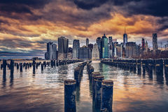 Brooklyn pier and pilings. Ominous clouds over Manhattan from Brooklyn sticks royalty free stock photos