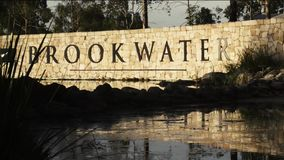 BROOKWATER, BRISBANE, AUSTRALIA - DECEMBER 20 2014: The Brookwater sign at the entrance of the estate and golf course. The Brookwater sign at the entrance of the stock footage