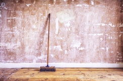 Broom against stripped drywall Stock Images