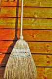 Broom for cleaning hanging on a wooden wall Royalty Free Stock Photo