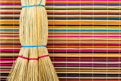 Broom on colorful background. Broom tied with bright ropes on motley multicolored background of bamboo sticks Royalty Free Stock Images