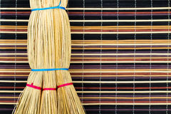 Broom on colorful background. Broom tied with bright ropes on motley multicolored background of bamboo sticks Stock Image