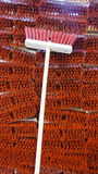 Broom in front of brooms. Pile of red brooms with a single broom in front Royalty Free Stock Images