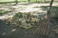 Broom and leaf on the ground in the park. Broom and leaf on the ground in a park Royalty Free Stock Photography