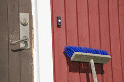 Broom leaning on a cottage wall Stock Photos