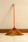 Broom leaning on the old gray wall Royalty Free Stock Photo