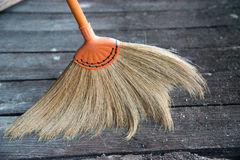 Broom made of grass blossom, sweeping dirt on wooden floor. Stock Photography