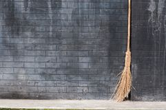 Broom. Old broom lean against black wall Stock Images