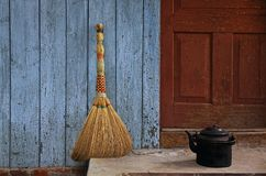 Broom and old teapot Stock Photos