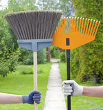Broom and rake. Male and female hand in gloves holding a broom and a rake in the garden Royalty Free Stock Photo