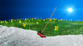 Spring Cleaning Time. A broom with snow and a greenfield with flowers Royalty Free Stock Photo