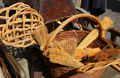 Broom of sorghum, carpet beater and wicker containers. Brooms of sorghum, a carpet beater and wicker containers for sale at flea market Stock Images