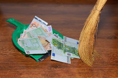 Broom sweep euros on wooden background. A lot of money, euros, inside washing machine, a simple concept for money laundering, Economy Concept Stock Photo