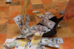 Broom sweep money in the scoop. Broom sweep a lot of dollar and euro bills in the scoop Royalty Free Stock Photo