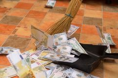 Broom sweep money in the scoop. Broom sweep a lot of dollar and euro bills in the scoop Royalty Free Stock Photos