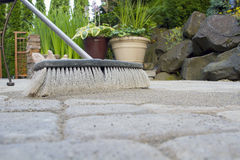 Broom Sweeping Sand into Pavers Low View Royalty Free Stock Photos