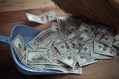 Broom sweeps dollars in garbage scoop Stock Image