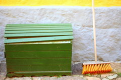 Broom on wall and wooden box outdoor - housework Royalty Free Stock Photos