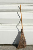 Broom on white wall Royalty Free Stock Photos