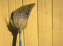 Broom on Yellow Wall. An old broom leaning against a yellow wall Stock Images
