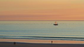 Broome lugger at sunset. A lugger's sails catch the colour of the sky Stock Photo