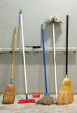 Brooms. Several used brooms leaned against grey wall Stock Photography