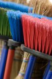 Brooms. Group of brooms with  long handle brush in green, red,  blue and natural colors with blurry background Stock Image