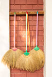 Brooms hang on wall. Stock Image