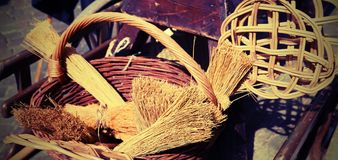 Brooms of sorghum, a carpet beater and wicker containers for sal. Brooms of sorghum, carpet beater and wicker basket for sale at flea market Royalty Free Stock Images